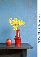 yellow narcissus in red vase and apple