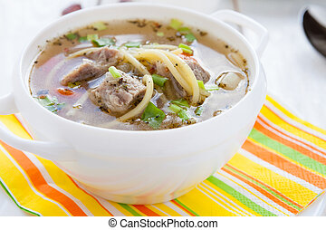 nutritious meat soup in a white tureen, closeup
