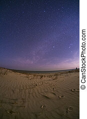 Milky Way over a sandy beach with the ocean in the...