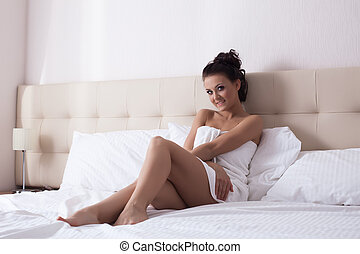Smiling young woman posing on hotel bed
