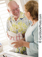 Senior Adult Couple Washing Dishes Together Inside Kitchen