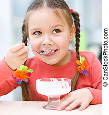 Little girl is eating ice-cream in parlor - Cute little girl...