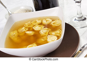 broth with ravioli over white tablecloth