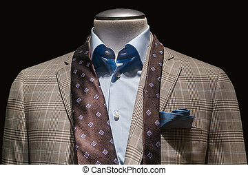Close-up of a tan checkered jacket with blue shirt, untied...