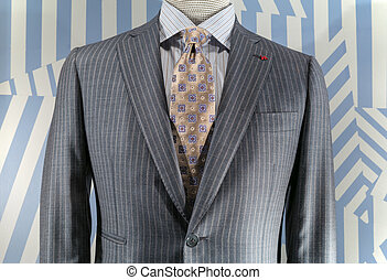 Close-up of a light gray striped jacket with blue striped shirt and patterned beige tie.