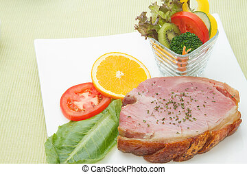 Smoked ham stack with fruit and vegetable salad on the white plate