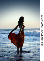 Beach Woman - Woman silhouette on the beach holding her...