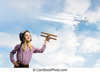 girl in helmet pilot playing with a toy airplane - little...