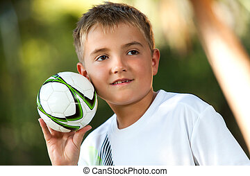 Boy holding small handball - Portrait of cute boy holding...