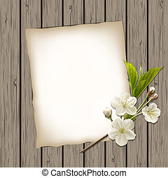 Blank paper with blossoming cherry branch on wooden...
