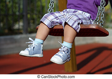 Feet of unrecognizable baby swinging on playground - Feet of...