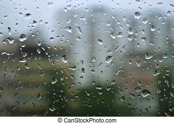 rain drops on a window and mystic silhouette of city