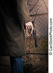 Hand with gun  - Male Hand with gun (revolver) outdoor.