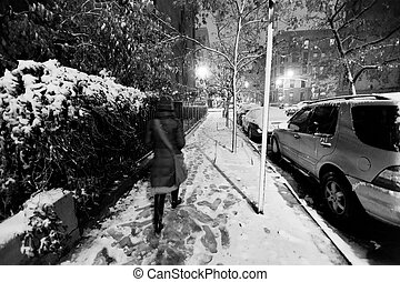 Lone woman walking on the snow covered pavement of a Harlem...