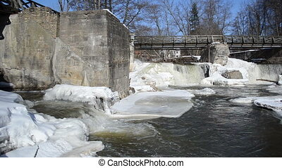river waterfall bridge - ice frozen river banks between...