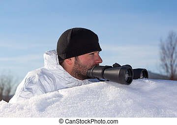 Scout in white camouflage coat with binoculars on white snow