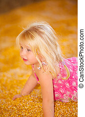 Child in Fall Harvest Corn - Pretty Young Child Playing in...