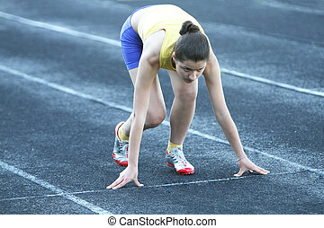 Athletic teenage girl in start position on track