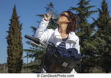 Mid aged woman biker drinks water