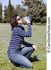 Mid aged woman relaxing on grass with a bottle of water,...