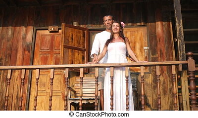 An attractive happy diverse couple in front of their home in...