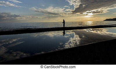 Fisher man with fishing rod silhouette on the beach at...