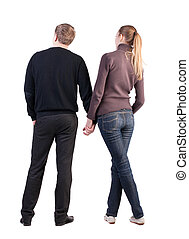 Back view of young couple (man and woman) hug and look into...