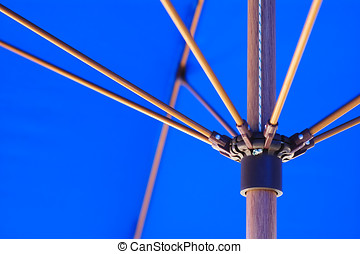 Parasol detail - Close-up of inside of blue parasol and wood...