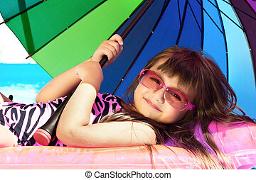 little girl on a pink mattress with a swimming pool