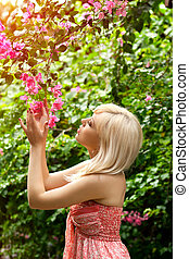 Portrait of a beautiful girl in the garden with tropical flowers