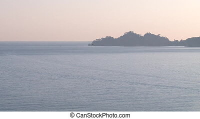 Open sea at sunset with peninsula - Open sea at a hazy...