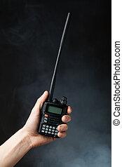 professional walkie-talkie radio in hand in smoke