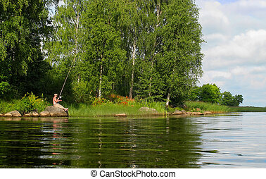 comfortable fishing - angler sitting on the stone