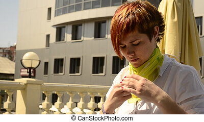 young woman tying a scarf sitting