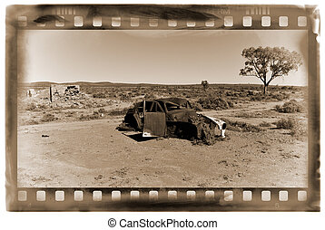 old car in the desert - an old car rusts away in the hot...