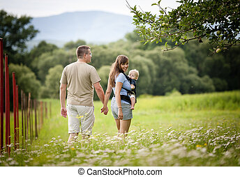 Family on the farm - Family walking in the field with baby...