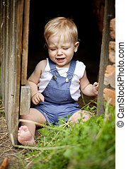 Family on the farm - Little boy is siting in the wooden...