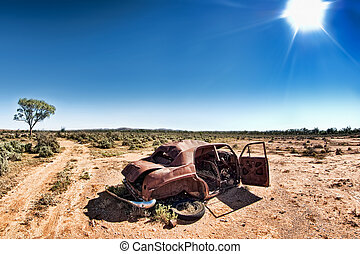 under a hot sun - a car rusts away under a hot sun in the...