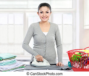 woman ironing clothes - portrait of Happy young beautiful...