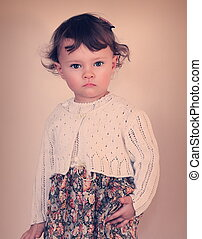Fashion baby girl posing in modern dress. Photo in vintage color style