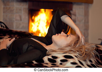 The girl is heated at a fireplace - series of the beautiful...