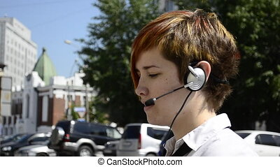 Business woman says through the headset outside