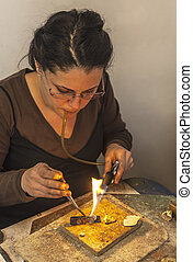 Jewellery Making - Female jeweller blowing a torch to melt...