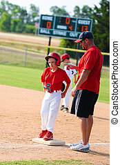 Baseball player and baseball coach at first base - Baseball...