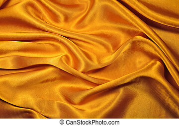 A gold fabric. - A rich gold folded fabric background.
