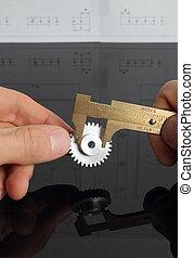 Man measuring cogwheel ony hands