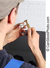 Man measuring cogwhell in front of a drawing