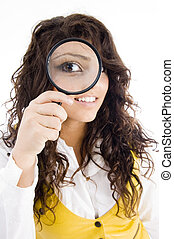 young girl holding magnifier and showing her magnified eye...