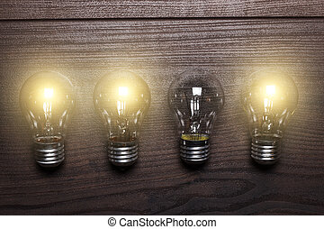 glowing bulbs weak link concept on wooden background -...