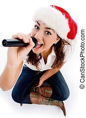 model holding karaoke and wearing christmas hat against...